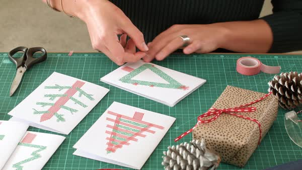 Woman hands making unique xmas cards, christmas holiday seasonal decor decorations traditional colours and pine cones Royalty-free stock video