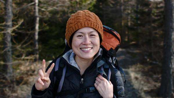 Happy natural smiling portrait of active woman making peace sign outdoors in forest with hiking backpack Royalty-free stock video