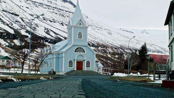 Small Icelandic town Seydisfjordur, East Iceland, church with snowy winter landscape in background Royalty-free stock video