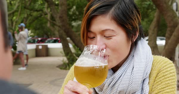 Young asian chinese woman drinks beer with friend at restaurant outdoors Royalty-free stock video