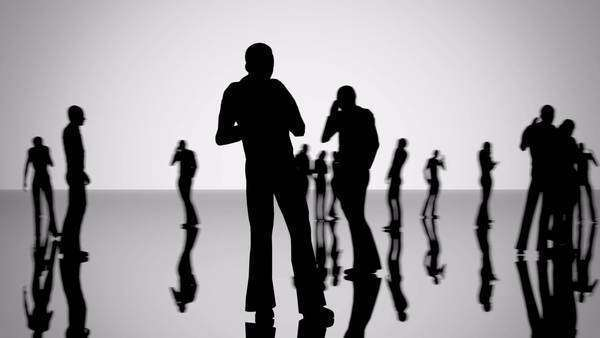 Silhouettes of a crowd of people walking on a reflective surface. Close-ups of random people. Royalty-free stock video