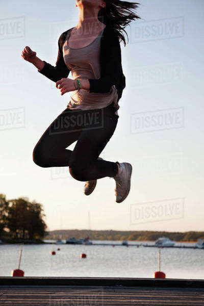 Teenage girl enjoying freedom by jumping on pier Royalty-free stock photo