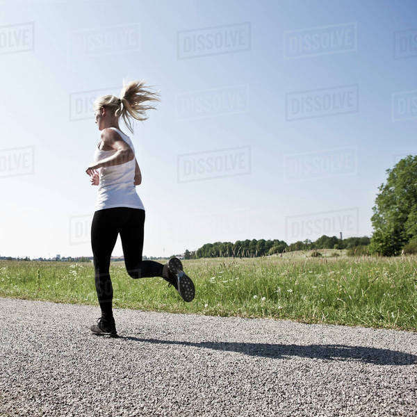 Full length of young woman jogging on road Royalty-free stock photo