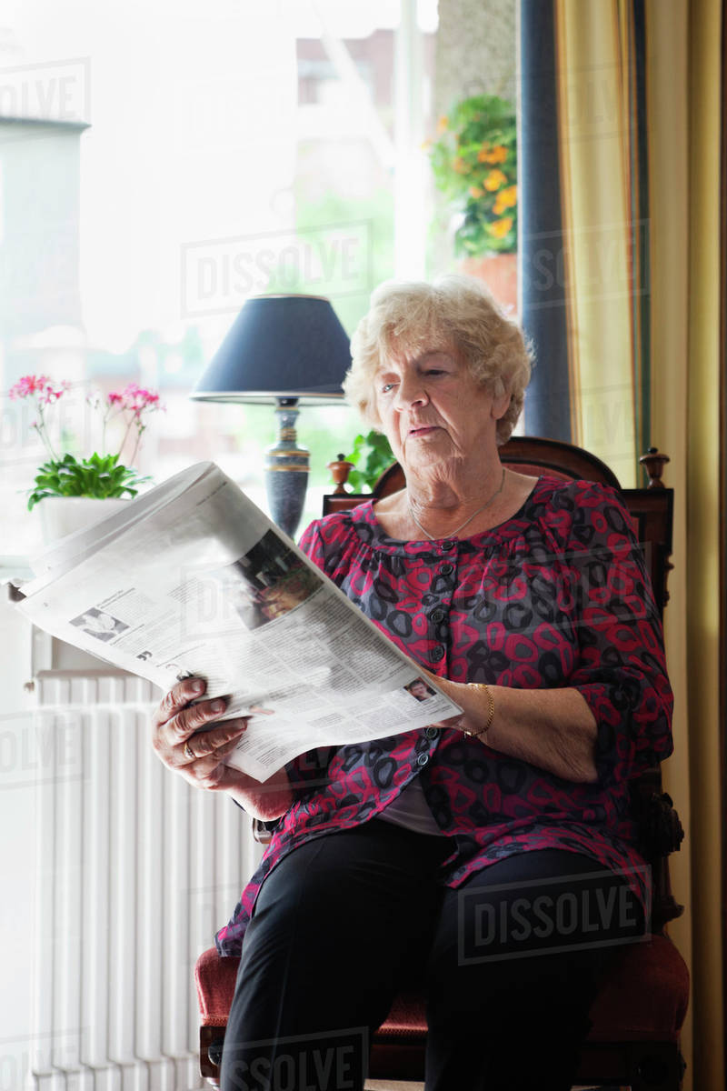 relaxed senior woman reading newspaper at home - stock photo - dissolve
