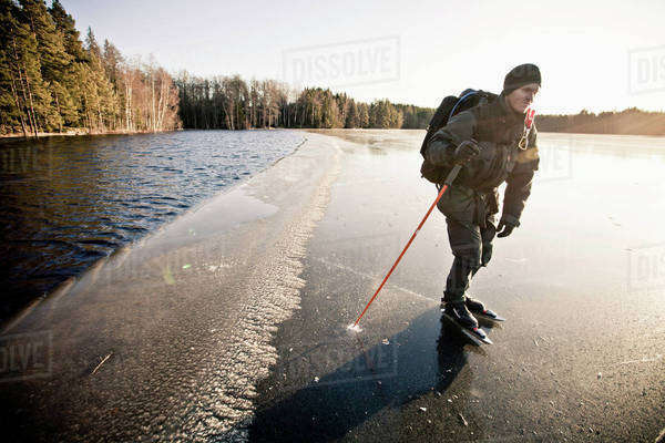 Mid adult man doing ice-skating on part frozen ice near lake Royalty-free stock photo