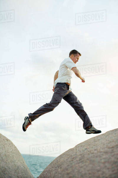 Full length of man jumping over rocks Royalty-free stock photo