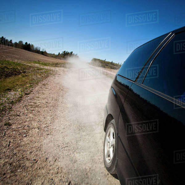 Black car moving fast on dirt road while blowing dust in air Royalty-free stock photo