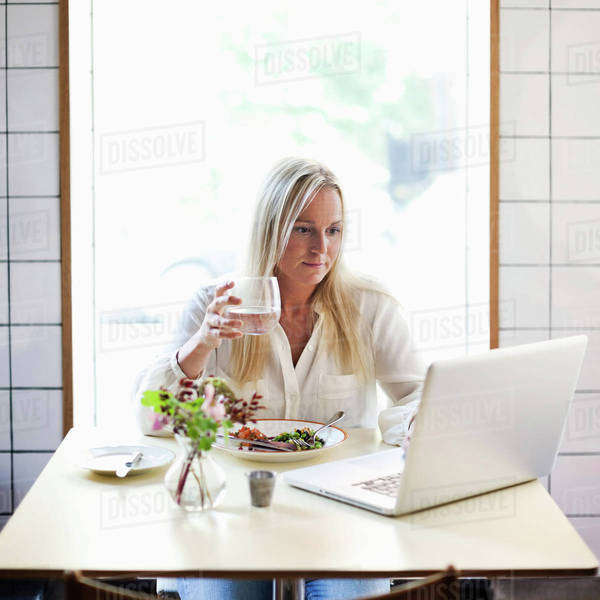 Mid adult woman using laptop while holding glass of water at restaurant table Royalty-free stock photo
