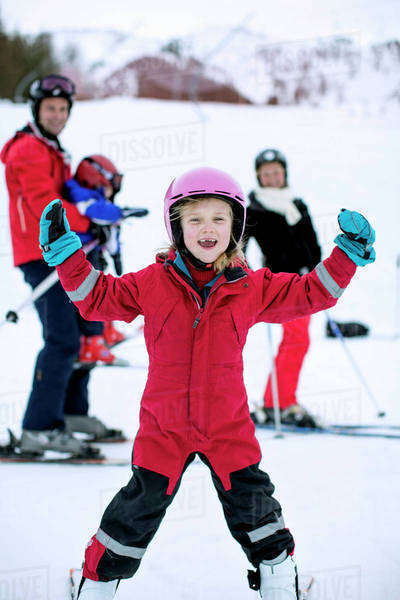 Portrait of happy girl enjoying skiing with family in background Royalty-free stock photo