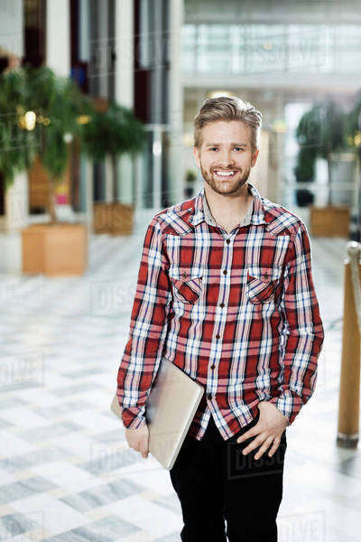 Portrait of happy young businessman with laptop standing at office Royalty-free stock photo