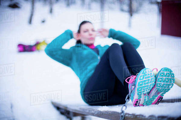 Mid adult woman doing sit-ups ob bench in snow Royalty-free stock photo