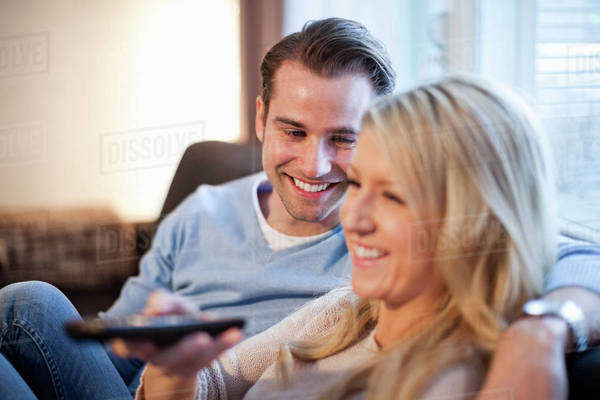 Mid adult man looking at woman watching TV Royalty-free stock photo