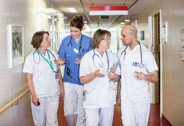 Team of doctors discussing while standing in hospital corridor Royalty-free stock photo