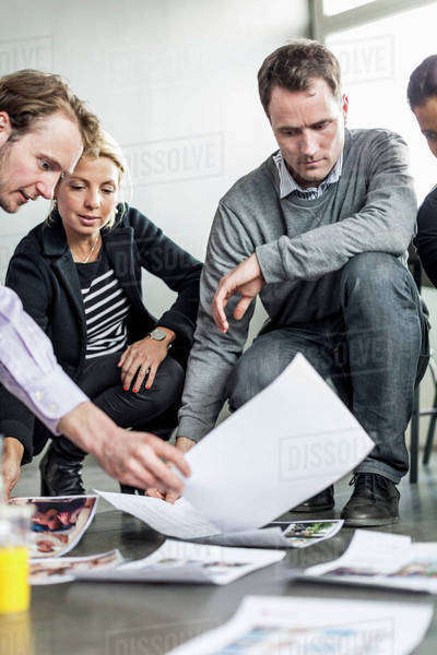 Business colleagues crouching while looking at photographs in office Royalty-free stock photo
