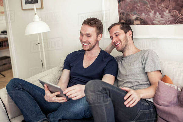 Happy homosexual couple using digital tablet together on sofa at home Royalty-free stock photo