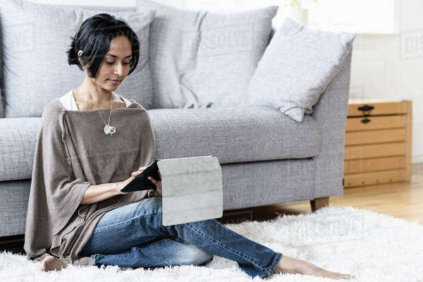 Mid adult woman using digital tablet while sitting on rug in living room Royalty-free stock photo