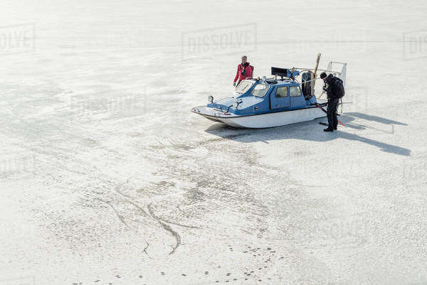 Men in skating wear standing by speedboat on frozen lake Royalty-free stock photo