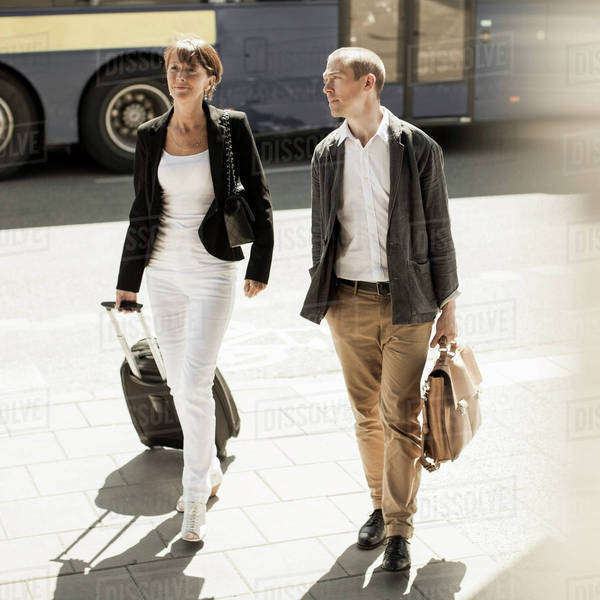 Business people with luggage walking on street Royalty-free stock photo