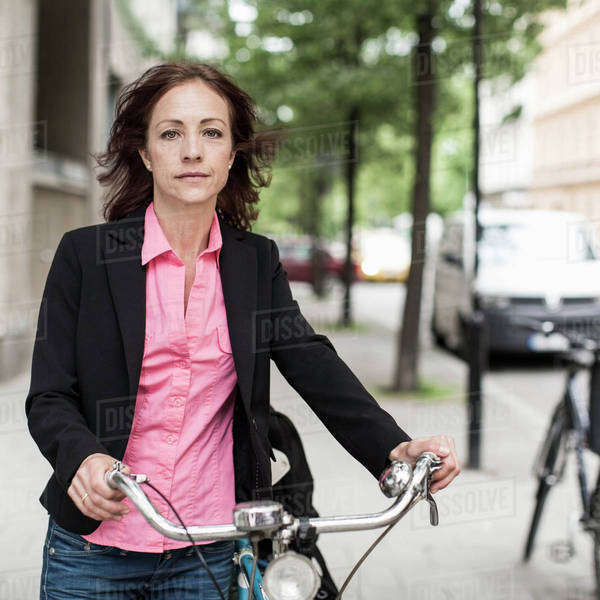 Portrait of confident businesswoman with bicycle standing on sidewalk Royalty-free stock photo