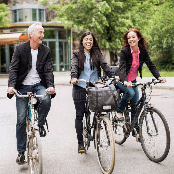 Happy business people riding bicycles on street Royalty-free stock photo
