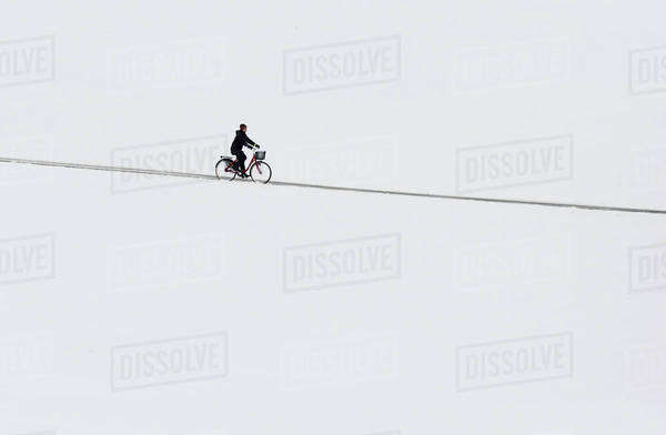 Woman cycling during winter Royalty-free stock photo