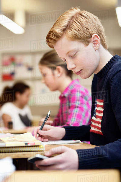 High school student using mobile phone while studying in classroom Royalty-free stock photo