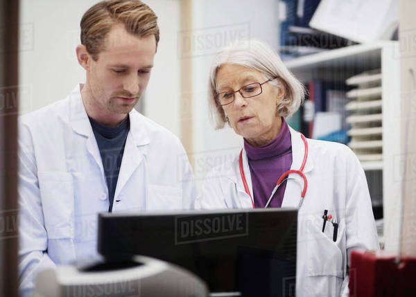Senior female doctor with male colleague using computer in examination room Royalty-free stock photo