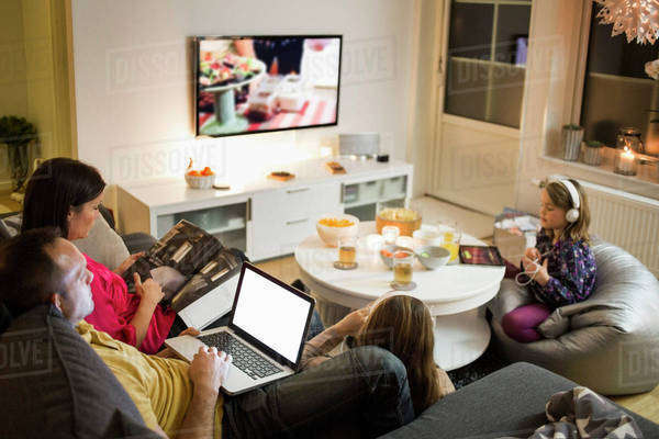 Family using technologies in living room Royalty-free stock photo