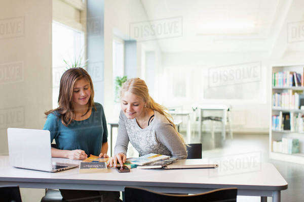 Teenage girls using mobile phone at table in school library Royalty-free stock photo