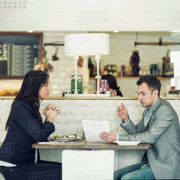 Side view of businessman with female colleague discussing at restaurant table Royalty-free stock photo