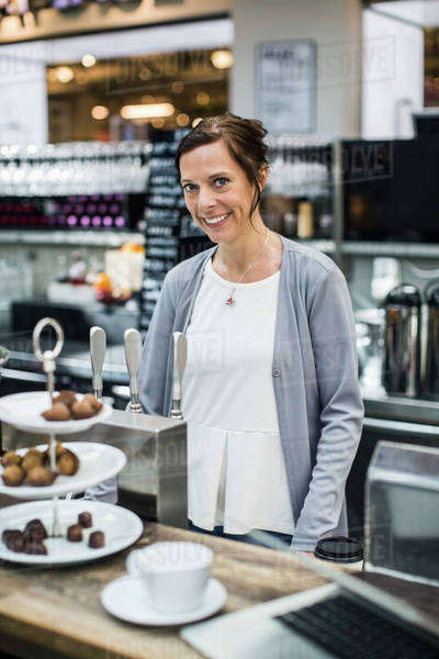 Portrait of smiling mature female owner at cafe counter Royalty-free stock photo