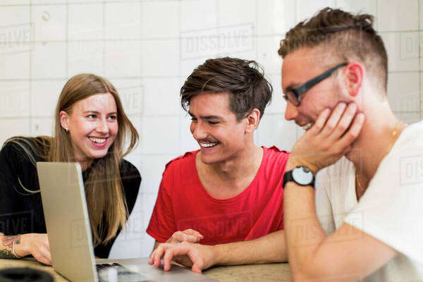 Happy young business people using laptop in creative office Royalty-free stock photo
