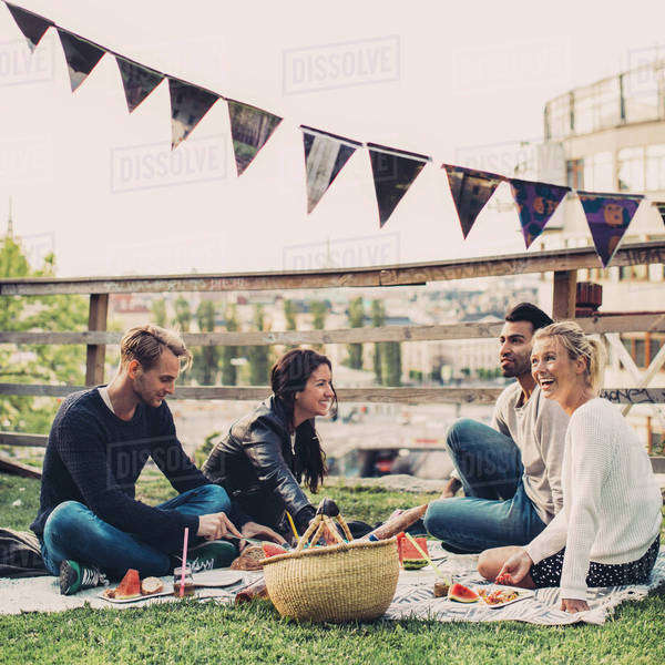 Happy friends enjoying picnic on roof garden Royalty-free stock photo