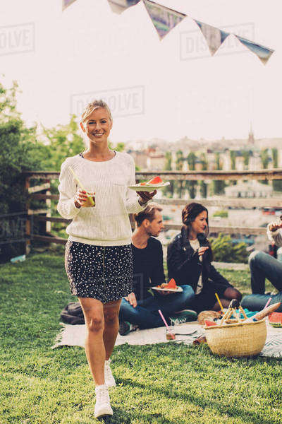 Portrait of happy woman with breakfast walking at rooftop party Royalty-free stock photo