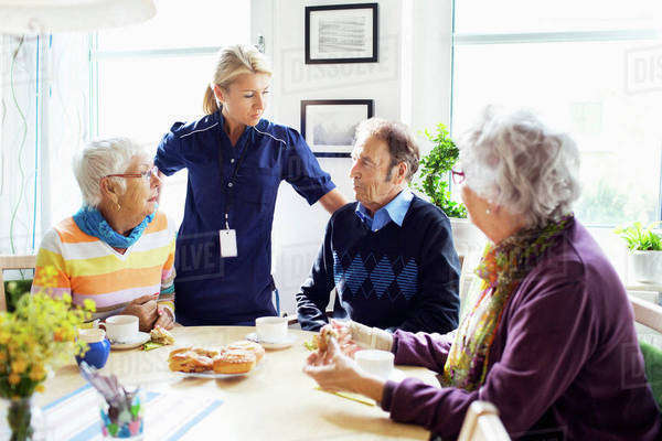 Female caretaker with senior people discussing at breakfast table in nursing home Royalty-free stock photo