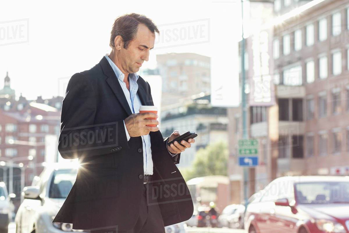 Businessman using mobile phone and holding disposable coffee cup while walking on city street Royalty-free stock photo
