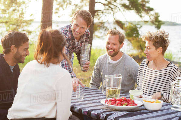 Group of friends enjoying while having lunch at lakeshore Royalty-free stock photo