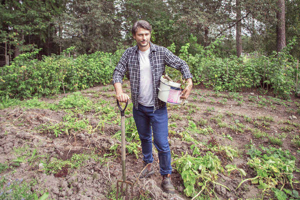Full length portrait of confident man with gardening fork and bucket at organic farm Royalty-free stock photo