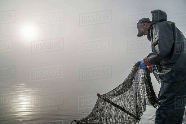 Side view of fisherman working with net on sea in foggy weather Royalty-free stock photo