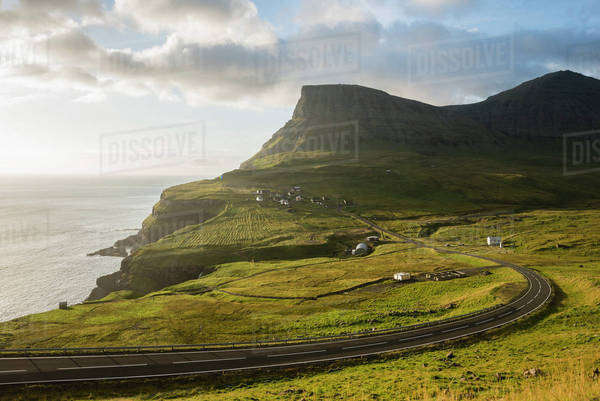 Grassy landscape and mountain by sea against sky Royalty-free stock photo