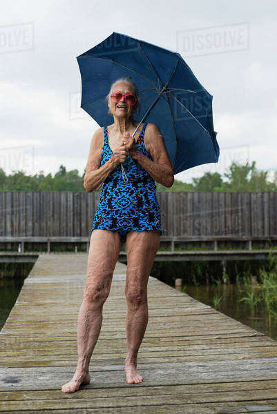 Portrait of happy senior woman in swimwear holding umbrella while standing boardwalk Royalty-free stock photo