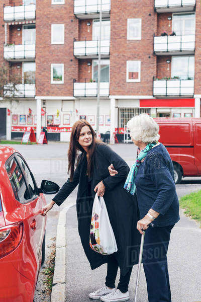 Young woman opening car door for grandmother on city street Royalty-free stock photo