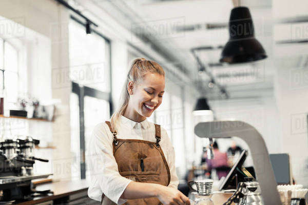 Happy female barista preparing coffee at cafe Royalty-free stock photo