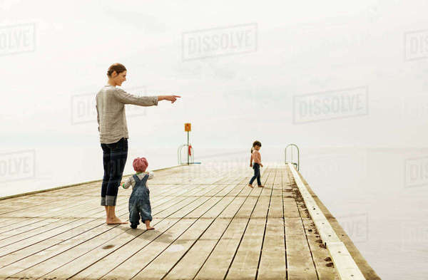 Mother showing something to baby girl while standing on pier at sea against sky Royalty-free stock photo