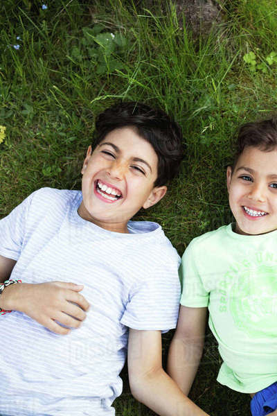 Directly above shot of playful boys lying on grassy field Royalty-free stock photo