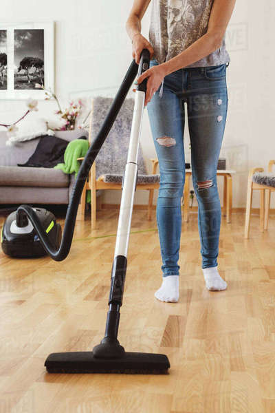 Low section of teenage girl using vacuum cleaner on hardwood floor in living room Royalty-free stock photo