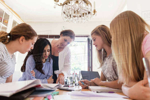Mature woman helping teenage girls in doing homework at home Royalty-free stock photo