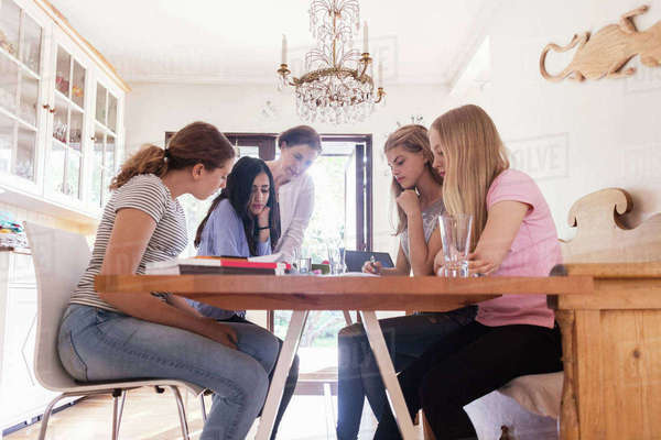 Mature woman assisting teenage girls in doing homework at home Royalty-free stock photo