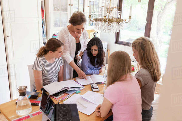 Woman assisting teenage girls in doing homework at home Royalty-free stock photo