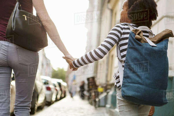 Midsection of woman holding hands with daughter while walking on sidewalk in city Royalty-free stock photo
